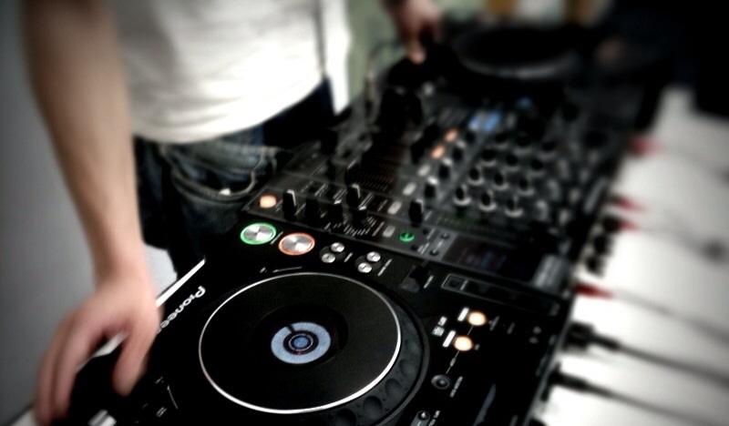 DJ steht am Mischpult und legt Musik auf