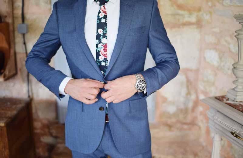 Bräutigam in modernem blauem Hochzeitsanzug mit geblümter Krawatte