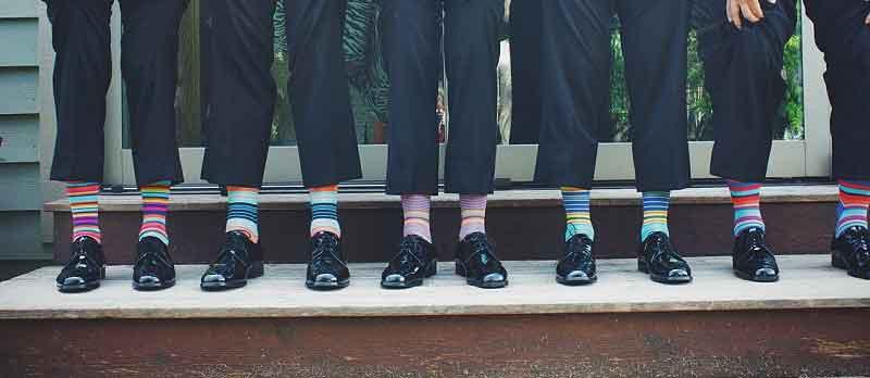 Braeutigam und Trauzeugen in Hochzeitsanzug mit bunten Socken